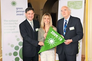 Geoff Jones and Roger Evans, who manage The Roger Lewis Woodland Garden, receive their award from TV presenter Michaela Strachan.