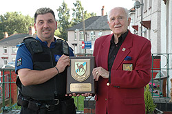 PCSO Neville Davies, from the Bargoed Neighbourhood Policing Team, is presented with his plaque by Gran Davies of the Canal Zoners group.
