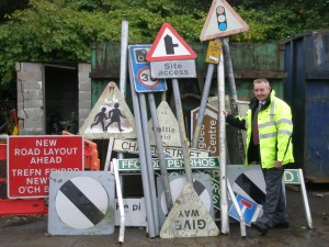 Cllr Rob Gough with a selection of signs that have been recently removed from the roads in Caerphilly County Borough.