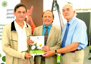 Roger Evans (left) and Geoff Jones (right) from the Oakdale and Penmaen Community Partnership receive their Green Pennant Award at the Royal Welsh Show