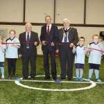 Children from Brithdir Bluebirds FC help the Minister for Culture and Sport, the Mayor of Caerphilly County Borough Council and Cllr Dave Poole cut the ribbon.