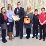 June Thomas (centre left) presented the defibrillator to St Martin's School