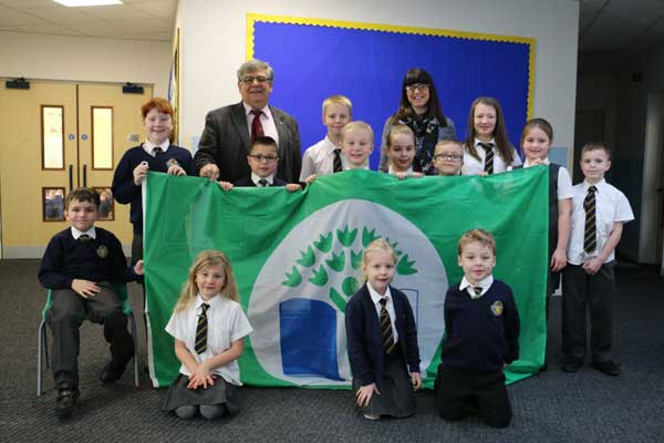 GREEN FLAG: The pupils of Ysgol Gymraeg Penalltau with Cllr Ken James and headteacher Andrea Woods