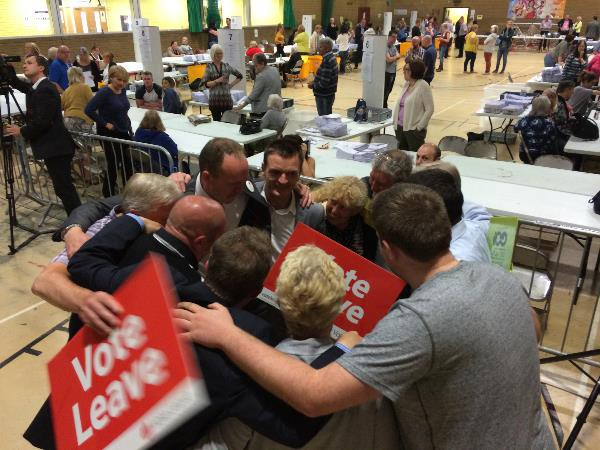 Leave campaigners celebrate in a huddle at Caerphilly Leisure Centre