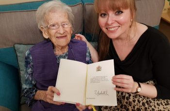 Delyth Jewell and her grandmother with card from The Queen