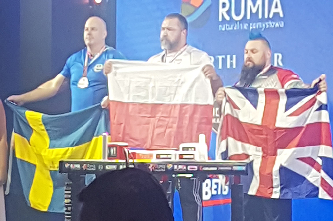 Arm wrestler Dean Bolt, right, on the medal podium in Rumia, Poland
