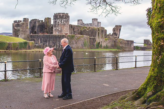 The happy couple pose for a photo in front of Caerphilly Castle