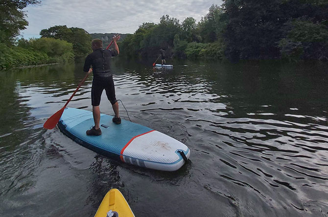 Youngsters part of the Creazione in the Community scheme paddle boarding on the River Taff