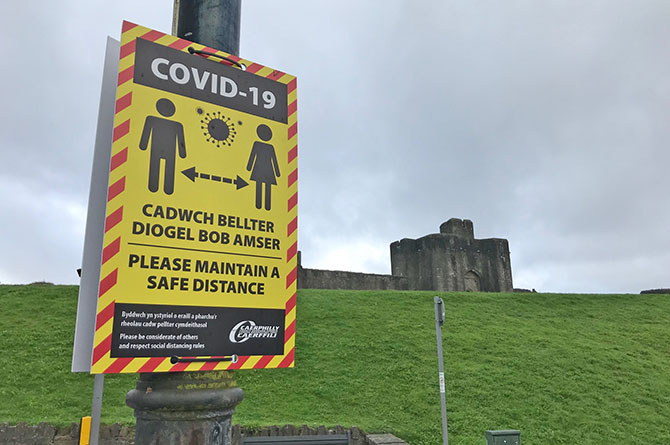 A social distancing warning sign near Caerphilly Castle