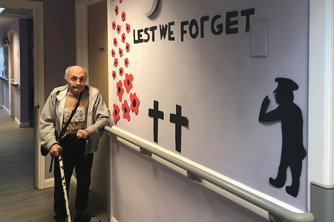 Ty Clyd resident Gaz standing next to a Remembrance mural