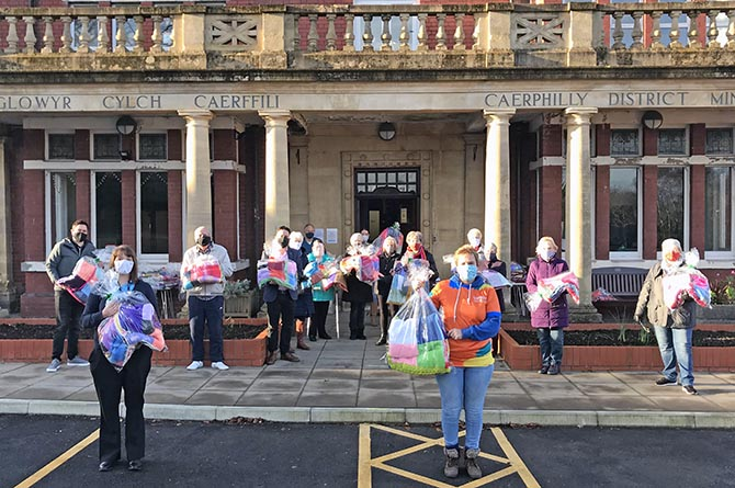 Knitting volunteers with their blankets outside Caerphilly Miners' Centre