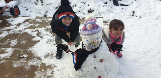 Osian and Seren with their snowman, Charlie