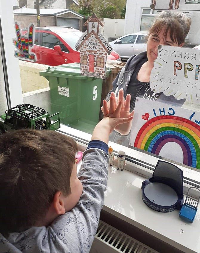 Suzanne Allen giving ten-year-old Aaron Hackney a 'high five' through the window