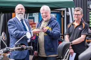 Norman Hyde, left, presents the ignition key to Simon Weston, centre, and Hank Hancock of Trike Design